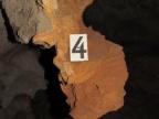 Fragment skorodowanej ściany jaskini z wystającym wiszarem zbudowanym z dedolomitu (znaczek ma 5 cm wysokości). Fot. Andrzej Tyc