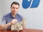 Mgr Dawid Surmik, doktorant z Wydziału Nauk o Ziemi, prezentuje częściowo zachowany szkielet triasowego morskiego gada sprzed 245 mln lat. Fot. Sekcja Prasowa UŚ
