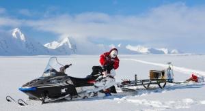 Naukowiec przewożący sprzęt badawczy na saniach śnieżnych