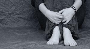 fragment osoby, która rękami trzyma przyciągnięte do ciała nogi