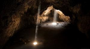 Widok jaskini oświetlonej wpadającym do niej z góry światłem