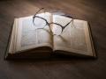 otwarta książka, na której leżą okulary