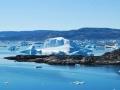 Fotografia przedstawia Fiord Sermilik na wschodnim wybrzeżu Grenlandii. Na kolejnych planach woda i nagi ląd. W wodzie znajdują się większe i mniejsze fragmenty lodu