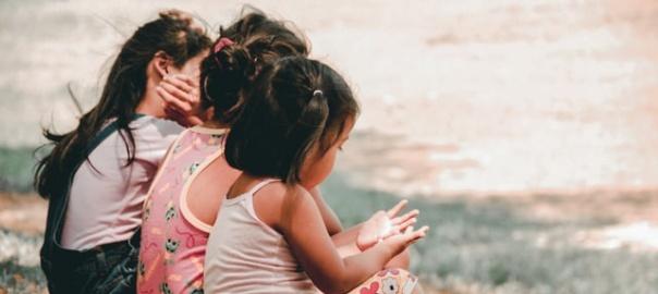 trzy dziewczynki siedzące nad brzegiem wody