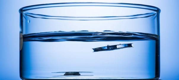 Dwie metalowe blaszki o tej samej wadze osadzone na dnie naczynia (University of Rochester photo / J. Adam Fenster)