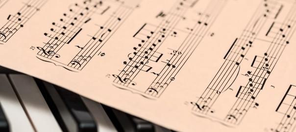 kartka z nutami leżąca na klawiszach fortepianu